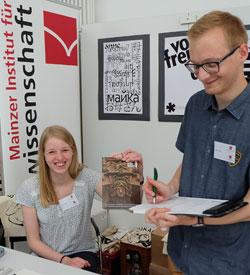 """""""Jawohl, da machen wir gerne mit!"""", zwei Studenten der Buchwissenschaften unterzeichnen auf der Minipressenmesse die Petition Altes Gericht. © DVG – massow-picture"""
