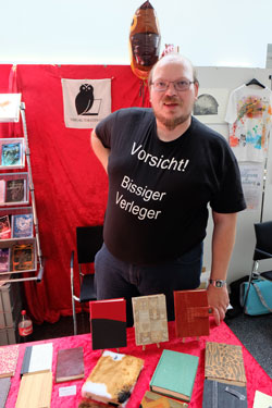 Thorsten Low verlegt vor allem Phantasik-Bücher, hier präsentiert er seine mit  Recycelingstoff – wie einer Jeans oder Slip - überzogenen Tagebuch-Buchcover. © massow-picture