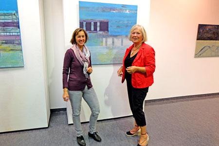 """Kunstdozentin Petra Ernsperger (li.) ist stolz auf ihre inzwischen so erfolgreiche und talentierte Schülerin Elly Zindler, hier bei der Vernissage der Ausstellung """"Linien - Schriftlinien"""" im Forum der Mainzer Volksbank. Im Hintergrund Elly Zindlers Werk """"Am Pool"""" Acryl auf Leinwand, Mischtechnik. © massow-picture"""