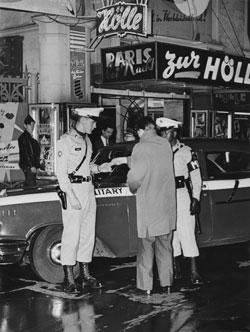 """""""Nachtleben, 1960""""  © ISG/F. Frischmann, S7FR_254 In den fünfziger Jahren entwickelte sich im """"Flussgebiet"""" des Bahnhofsviertels, zwischen Mosel- und Weserstraße, ein Vergnügungszentrum, in dem sich deutsche und internationale Messebesucher, Bewohner der Stadt und ihrer Umgebung und amerikanische Militärangehörige mischten. An den Wochenenden, vor allem am Pay-day, wenn sich die Soldaten in Gaststätten, Musik- und Striplokalen sowie Bordellen amüsierten, gab es für den Streifendienst der amerikanischen Militärpolizei häufig Anlass einzuschreiten."""
