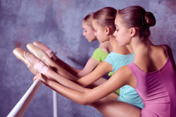 Ballerinas stretching on the bar Fotolia © master1305
