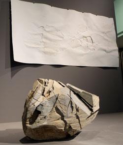 """""""Kopf, Teil aus dem Ganzen – liegend"""", 2016, Holz, gekalkt. Er wurde aus der Skulptur """"Ausgehöhlter Stamm – liegend"""", entnommen, gekalkt, geschmirgelt und abgedruckt in einem besonders dichtem Filterpapier, welches im Hintergrund angebracht ist. Foto © massow-picture"""
