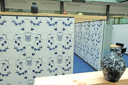 Siebdrucke von Rieke Köster greifen die Farbe des Teppichbodens auf und bedecken sämtliche Innenseiten sowie eine Außenwand. Auf die Seitenwände aufgelegte Holzbalken schlie- ßen den Raum nach oben optisch ab. Sie fungieren als Träger von Vasen, Schalen und anderen Gefäßen. Foto:© massow-picture
