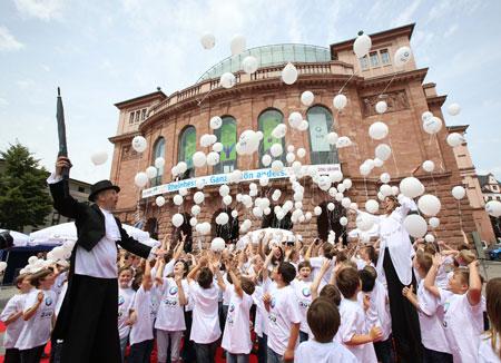 Mädchen und Jungen des Mainzer Domchors sowie des Mädchenchors am Dom und St. Quintin lassen vor dem Mainzer Staatstheater hunderte Rheinhessen-Luftballons anlässlich der 200-Jahrfeier aufsteigen. Foto: ©  Agentur Bartenbach