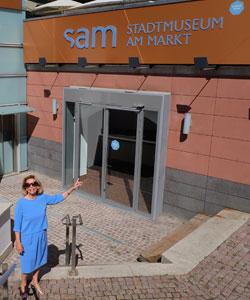 Kulturdezernentin Rose-Lore Scholz erläutert die dem Umfeld angepasste dezente Farbwahl bei Schriftzug und Eingangsbereich. Das sam kann Brücke zu  einem großen Stadtmuseum sein.  Foto © massow-picture