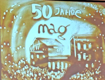 """Die russisch-deutsche SandArt-Künstlerin Natalya Netselya faszinierte die über 250 Jubiläumsgäste mit ihrer aus Sand hingezauberten, auf Großleinwand projizierten  Restrospektive """"50 Jahre MAG-Firmengeschichte"""" . Die Abbildung zeigt das Abschluss-Bild. Foto: Diether v. Goddenthow © massow-picture"""