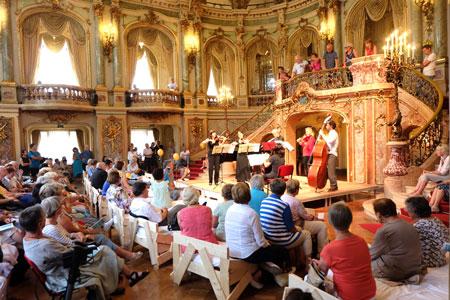 """Mozart-Impressionen beim Theater-Biennale-Fest. Besucher sitzen  auf den Holzbetten im zum """"Biennale-Grand-Hotel"""" umgewidmeten Foyer des Großen Hauses. Foto: Diether v. Goddenthow © massow-picture"""