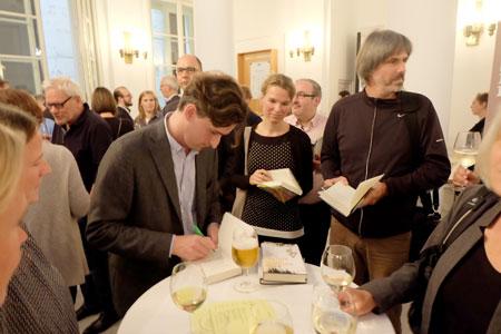 """In der Pause, bei guten Gesprächen und einem Glas Wein, konnten die am Bücherstand erworbenen Werke signiert werden. Das Bild zeigt Reinhard Kaiser-Mühlecker beim Eintrag in sein Werk """"Fremde Seele, dunkler Wald"""" (S.Fischer, Frankfurt)."""