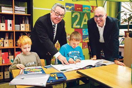Vorstandsvorsitzender Peter E. Eckes (links) und Konrektor Lars Strömel (rechts) erkunden gemeinsam mit den Schülern das Rheinhessen Mal- und Rätselbuch