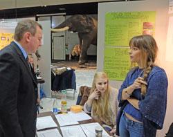 """Dr. Sven Soff, Regionalwettbewerbsleiter und Juror lässt sich von Lena Magerl (18) und Jamila Schiel (18) das """"Jagdverhalten von Jemen Chamäleons"""" erklären.  Foto: Diether v. Goddenthow"""