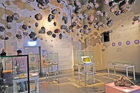 Symbolisch hängen die auf die Erde niederprasselnden Meteoriten  an der Decke, darunter die Show-Vitrinen und an die Wänden die Infotexte. Foto:. D. v. Goddenthow © atelier-goddenthow