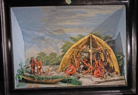 Maquett de carbet (1839) versetzt die Betrachter in ein karibisches Indianerlager, mit unter Kinder, Hunde  und Vögel. In einem üppigen Wald sieht man Menschen, die vom Fischen zurückkehren, während andere in Hängematten  ruhen oder ein Gürteltier am Lagerfeuer schlachten.  Foto: Diether v. Goddenthow