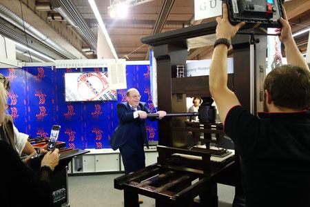 """Dreharbeiten am Stand des Gutenberg-Museums: SWR-Moderator Denis Scheck demonstriert den Zuschauern des Kulturmagazins """"Kunscht!"""" an der rekonstruierten Gutenberg-Presse, wie vor 550 Jahren gedruckt wurde. Foto: Gutenberg-Museum Mainz"""