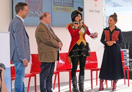 Mira Valentin (Mitte) erhält für ihr Buch Der Mitreiser und die Überfliegerin den Kindle Storyteller Award. Foto: Diether v. Goddenthow