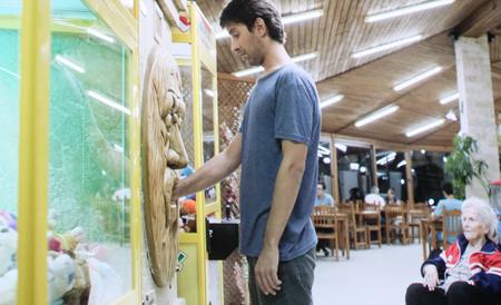 """Aus Eröffnungsfilm The Gulf: Selim – dreißigirgendwas, erfolglos, geschieden und gestrandet in Istanbul, hofft eine gute Zukunftsprognose am """"Wahrsageautomat"""", in dem er seine Hand reinlegen muss."""
