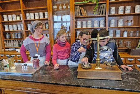 Historische Drogerie unter Anleitung in Kinderhand, hier an der Apotheker-Waage, wie sie einst üblich waren. © Foto: atelier-Goddenthow