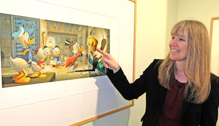 """Dr. Birgit Heide, Direktorin des Landesmuseum Mainz war früher selbst Disney-Fan. Hier vor einem Druck von Carl Barks Werk """"The golden Fleece"""". . """"Unsere Besonderheit liegt darin"""", so Dr. Birgit Heide, """"dass wir uns nicht nur mit einem Thema oder einem Schwerpunkt beschäftigen, sondern für sämtliche Bereiche der Kunst- und Kulturgeschichte relevant sind: Sei es die Archäologie, Gemälde und Grafiken, Skulpturen oder das Kunstgewerbe."""" Das Museum verfüge über reiche Bestände, so auch über 42 Arbeiten von Carl Barks, dem die Ausstellung einen kompletten Raum gewidmet habe.© Foto: Diether v. Goddenthow"""