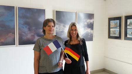 """(v.l.) Annette Thiergarten (Vorsitzende der Künstlergruppe Nahe) und Christine Simmich (Stadt Bad Kreuznach) vor dem Hintergrund des Traums: """"Imagine oder der Himmel ohne Fluglärm. © Foto: Christiane Kasper"""