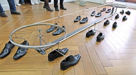 Isabell Ratzinger, Die Schuhe, 2017. Der Apparat Schuhe zieht zehn Paar Herrenschuhe, die an einem Seil befestigt sind, um zwei Fahrradfelgen. In einer nicht enden wollenden Kreisbewegung verfolgen sie einander ohne ihren Vorläufer je einholen zu können. ... Dieses Werk ist Teil der Ausstellung  bee bee nnz krr müü - der Titel der Ausstellung entstammt der Ursonate von Kurt Schwitters. Nur aus einzelnen Lauten bestehend ist das Gedicht ein Sinnbild für die Destruktion vorherrschender Sinngebung und bürgerlicher Ordnung um 1918. © Foto: Diether v. Goddenthow