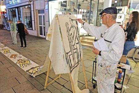 Aktionskünstler Bernd Schneider malt unaufhörlich auf eine Endlosrolle vor der Galerie Kunst Schäfer in der Faulbrunnenstrasse. © Foto: Diether v. Goddenthow