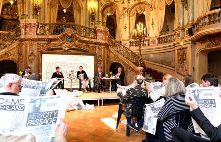 """Bei der Pressekonferenz wurden die Medienvertreter selbst zu Akteuren einer Art """"BAD-NEWS""""-Programm-Synchron-Lesung, einer Art """"Read-In"""", was Kuratorin Magdalena Ludewig ihrerseits smartphonefotografisch festhielt. Dieses Bild zeigt die """"Ad-hoc-Biennale-Lesegemeinde"""" mit Blick aufs Podium im Foyer des Staatstheaters beim Pressegespräch.  Die Biennale-Programmzeitung """"Bad News"""" wird es demnächst an vielen """"kulturellen Brennpunkten"""" der Stadt geben. © Foto: Diether v. Goddenthow"""