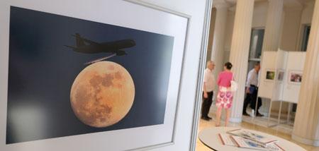 """Ausstellungs-Impression. Den Lufthansa-Flieger auf Kai Oliver Pfaffenbachs Foto """"Käsereibe"""", der beim Landeanflug auf Frankfurt/Main den Mond zu schrammen scheint, sieht man nur, wenn man sich die Ausstellung selbst anschaut."""