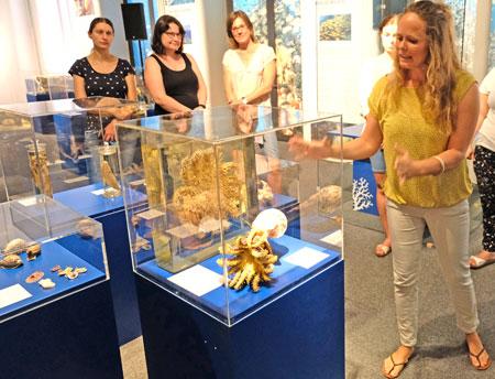 Stefanie Raddatz, Kuratorin der Ausstellung, erläutert hier das Modell eines Tritonshorns, welches einen Dornenkronenseestern verschlingt und einen Beitrag zur Verbesserung der Riffe leisten könne. © Foto: Diether v. Goddenthow