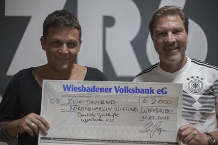 Sascha Burjan (links im Bild) konnte jetzt einen Scheck über 2.000 Euro an den 1. Vorsitzenden des Fördervereins Deutsche Sporthilfe Wiesbaden e.V., Andreas Steinbauer (rechts im Bild), überreichen. Foto: Tahar Jaber