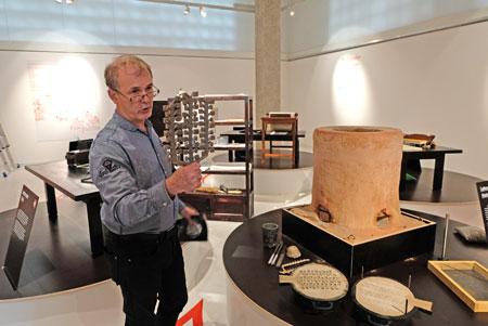 Dr Claus Maywald, Experte für fernöstliche Drucktechnik bei Gutenberg, demonstriert den historischen Metall-Lettern-Guss  Ostasiens. Zuvor wurden auf Holz geschriebene Lettern ausgesägt, die in Formsand gedrückt wurden. Zirka 1085 Grad heißes geschmolzenes Metall wurde in die Öffnung der zweiteiligen Gussform gegossen. Nach erkalten wurden die noch an den Gusskanälen hängenden Lettern herausgenommen (siehe in der Hand v. Dr. Maywald). © Foto: Diether v. Goddenthow