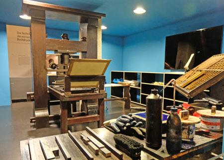 An Gutenbergs Druckerpresse, inmitten einer nachgebauten Druckerwerkstatt,  werden auch Druckvorführungen während der Ausstellungszeit  angeboten.  © Foto: Diether v. Goddenthow