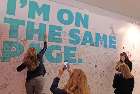 Junge Leute aus aller Welt schreiben ihre Botschaften zur Aktion I'm on the same page auf das große weiße Brett im Foyer der Halle 4.0. © Foto: Diether v. Goddenthow