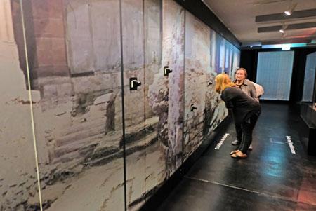 """Wer durch die zahlreich en Guckgläser der Archäologischen Wand schaut, erhält tiefe Einblicke in das Grabungsgeschehen in der St. Leonhardskirche und kann noch besser nachvollziehen, weswegen die Ausstellung """"Schätze aus dem Schutt"""" heißt. ©  Foto: Diether v Goddenthow"""