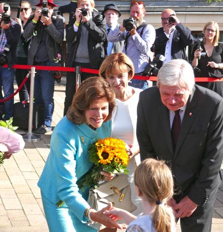 Kurz vor ihrer Weiterfahrt nimmt Königin Silvia noch einen Blumenstrauß eines kleinen Mädchen dankend in Empfang. Neben ihr Ursula und Volker Bouffier. ©  Foto: Heike  v Goddenthow