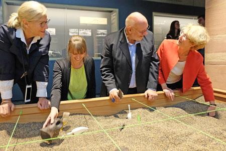 """Senckenbergs neue Grabungsstätte im kleinen Workshop-Bereich, gleich neben Diplodocus und Iguanodon, ist einem realen 'Bonebed' nachempfunden"""". Doris Manz-Wisser (Förderin), Kuratorin Larissa Goebel, Claus Wisser (Förderer)und Museums-Direktorin Dr. Katrin Böhning-Gaese zeigen schon mal wie es geht. ©  Foto: Diether  v Goddenthow"""