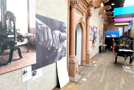 Mit einmaligen, hochvergrößerten Wandillustrationen und Original-Druckmaschinen hat das Gutenberg-Museum die Weimarer Werkstatt nachgebaut. Links auf dem Foto sind die Hände des ersten Werkstattleiters Lyonel Feiniger zu sehen. ©  Foto: Diether  v Goddenthow