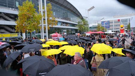 Buchmessebesucher mit aufgespannten Regenschirmen auf der Agora des Frankfurter Messegeländes. © Foto: Diether v Goddenthow