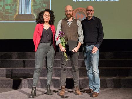 Internationaler Kurzfilm-Wettbewerb: Regisseur Thomas Johnson (Mi.) nahm den Preis für seinen Film IMBUED LIFE, den er gemeinsam mit Ivana Bošnjak realisierte, von der internationalen Jury (Brunna Laboissière und Burkhard Althoff) entgegen. / Foto: Peter R. Fischer