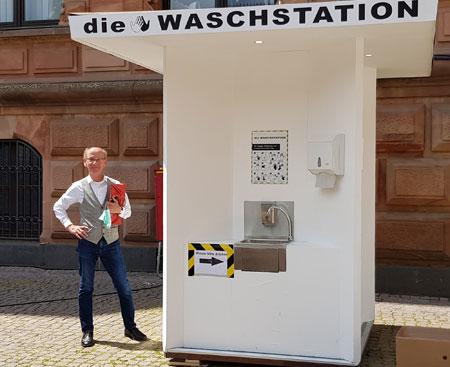 Seit vergangenem Mittwoch gibt es zwischen Wiesbadener Rathaus und Marktkirche diese Waschstation zum kostenlosen Händewaschen. Man muss nur wissen, dass der Wasserhahn mit dem Knie unterhalb des Waschbeckens geöffnet werden kann.  © Foto: Diether v. Goddenthow