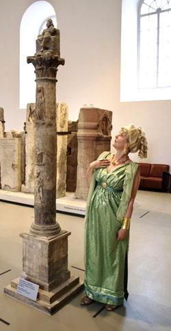 Dr. Judith König als Römerin Aurelia neben der Kleinen Jupitersäule.bringt Steine zum Sprechen Foto: GDKE RLP LMM, Kristina Péró