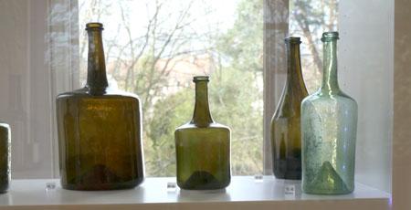 Historische Weinflaschen aus der Sammlung Degenhard May, kombiniert mit moderner Kunst aus Weinreben von Daniela Orben, im Museum Schlosspark © Foto: Heike v. Goddenthow
